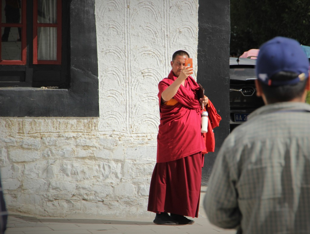 Tibetan monk taking a picture with his smartphone, while it looks like he is also carrying a tablet.